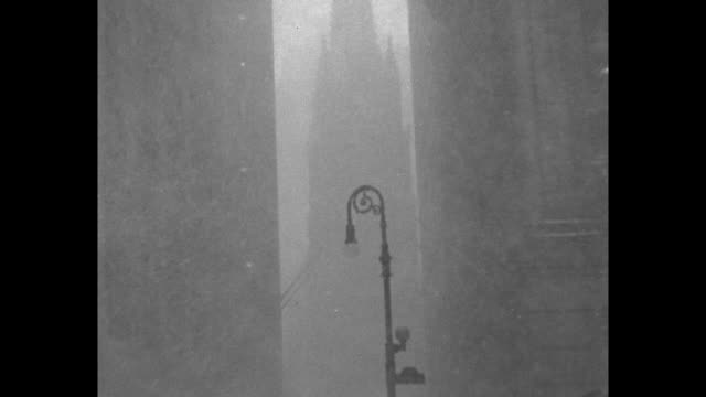 snowplows approach as they plow major thoroughfare / church spire seen between skyscrapers, obscured by falling snow; tilt down to street scene on... - turmspitze stock-videos und b-roll-filmmaterial