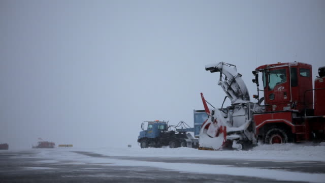 vidéos et rushes de snowplows move to clear airstrip during snowfall - montreal