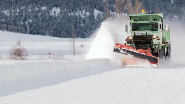snowplows scraping road in yellowstone national park, wyoming, in winter - snowplough stock videos & royalty-free footage