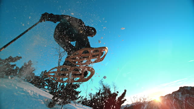 slo, mo, schneeschuh springen bei sonnenuntergang - wanderstock stock-videos und b-roll-filmmaterial