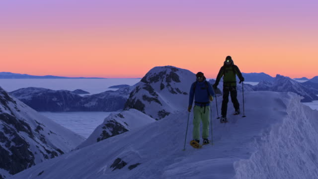 PAN Snowshoeing across a mountain ridge at dusk