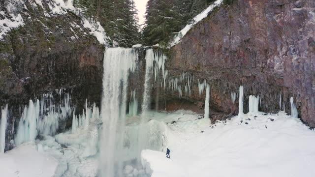 Snowshoer approaching waterfall