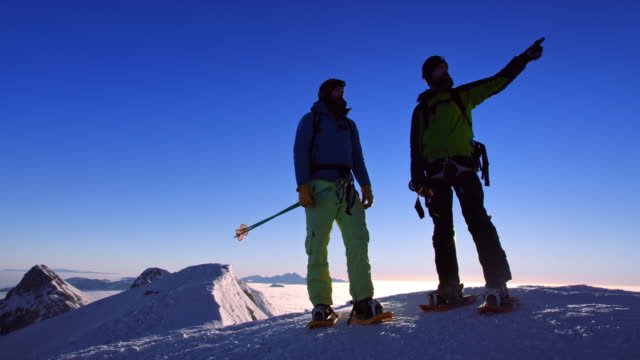 DS Snowshoers discussing routes on the mountain top at sunset