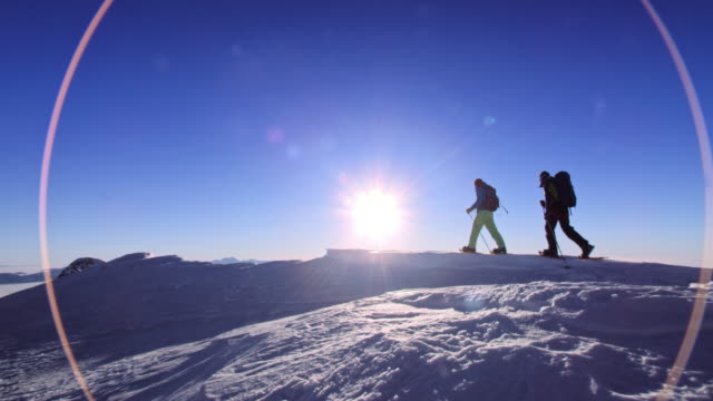 DS Snowshoers walking on a mountain top in sunshine