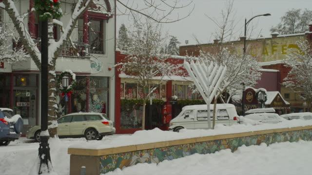 MEDIUM PAN snowy downtown street with Christmas and Hanukkah decorations, Ashland, Oregon