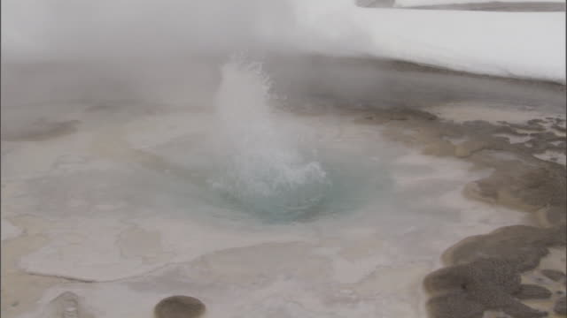 snowy ground and spurting geyser in pool, yellowstone, usa - geyser stock videos & royalty-free footage