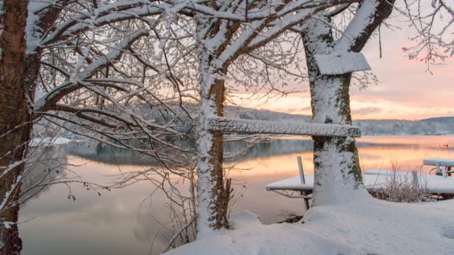 vídeos de stock, filmes e b-roll de snowy lake sunrise - lago reflection