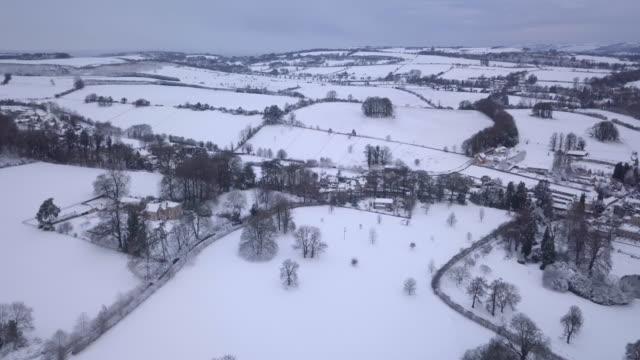 vidéos et rushes de snowy landscape of the rural cotswolds near christmas - patchwork landscape