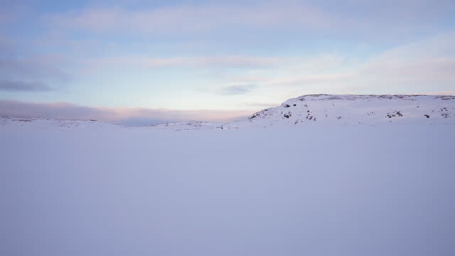 A snowy landscape to the horizon with partly cloudy blue sky