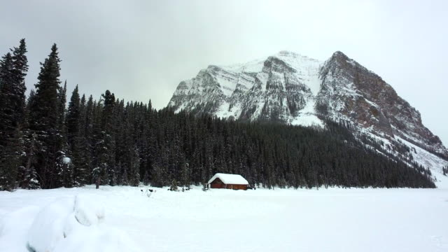 snowy log cabin & mountain valley / banff, canada - capanna di legno video stock e b–roll