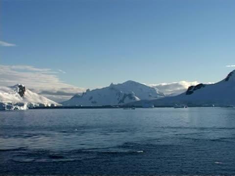wa snowy mountain coastline, sea water foreground, blue sky, sunny, antarctic peninsula - antarctic peninsula stock videos & royalty-free footage