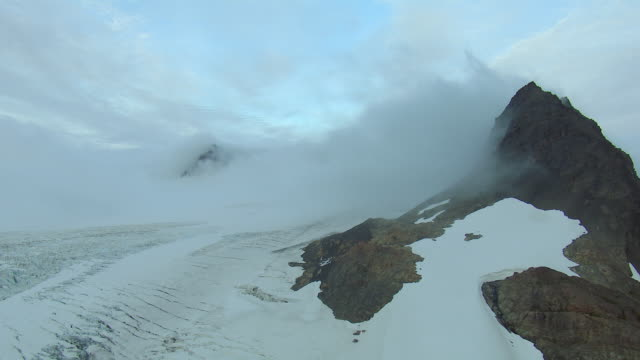 Snowy Mountain Peaks Shrouded With Mist