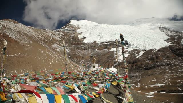 snowy mountains hinter bunten gebetsfahnen in tibet - klammer stock-videos und b-roll-filmmaterial
