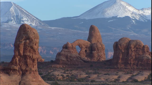 Snowy mountains rise behind Turret Arch in Arches National Park, Utah.