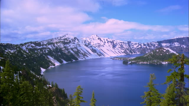 snowy mountains surround crater lake. - crater lake oregon stock videos & royalty-free footage