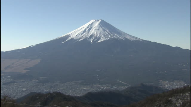 snowy mt. fuji casts a shadow over a valley and city at its base. - 山梨県点の映像素材/bロール
