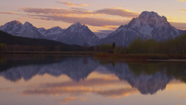 wide shot snowy mt moran and teton range with snake river at oxbow bend in foreground at sunset, grand teton national park, wyoming - mt moran stock videos & royalty-free footage