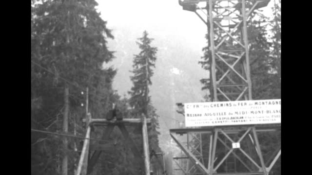 CU snowy peak of Mont Blanc / aerial cable towers with mountain in distance / MS construction materials move up cable on mountainside toward and past...
