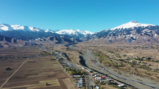 snowy scene of field and village and mountain / xinjiang uyghur autonomous region, china - 新疆ウイグル自治区点の映像素材/bロール