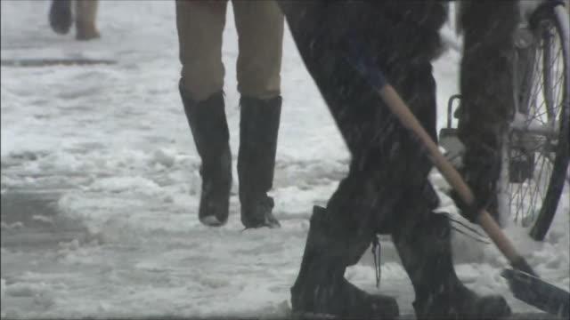 vídeos de stock e filmes b-roll de snowy sidewalk person shoveling snow person walking - pá para neve