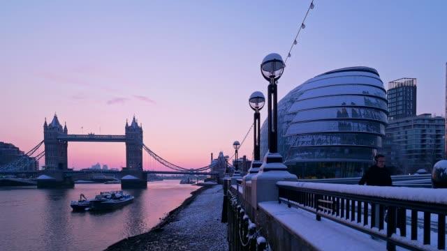 vídeos de stock, filmes e b-roll de a snowy tower bridge and river thames at dusk, london, uk - rio tâmisa