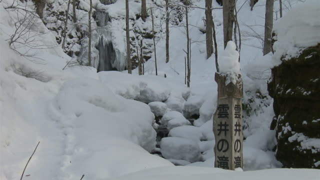 snowy waterfall and its sign, aomori, japan - oirase river stock videos & royalty-free footage
