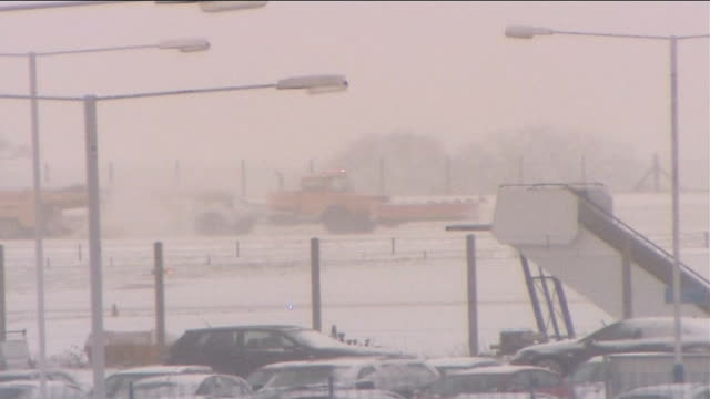 vidéos et rushes de snowy weather causes travel chaos luton airport plane on runway dissolve to snow ploughs along trying to clear runway int group of young male... - piste d'envol