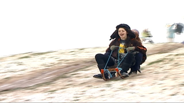 snowy weather causes travel chaos primrose hill good shot of two girls along down snow covered hillside on sleigh pan - sledge stock videos & royalty-free footage