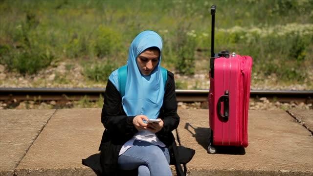 vídeos de stock, filmes e b-roll de tão chato esperando um trem... mulher muçulmana moderna na estação de trem - vestuário modesto