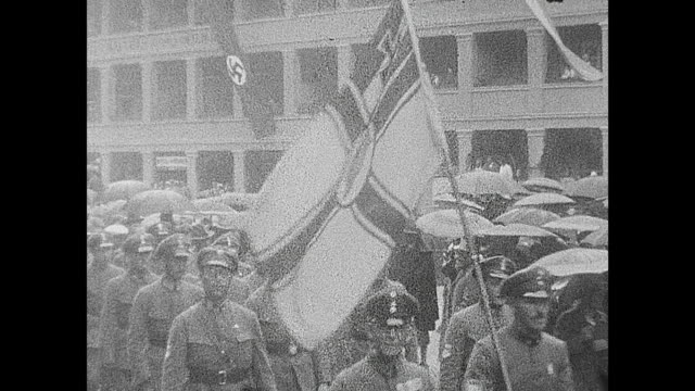 So called borderland demonstration in Oberstdorf 1933 everything filmed from one psition Nazis walking with flags through the city very big swastika...