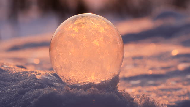 soap bubble in the snow in winter. ice patterns on the surface - eingefroren stock-videos und b-roll-filmmaterial