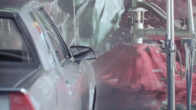 soap sprays and brushes rotate as a car moves through a car wash. - biltvätt bildbanksvideor och videomaterial från bakom kulisserna