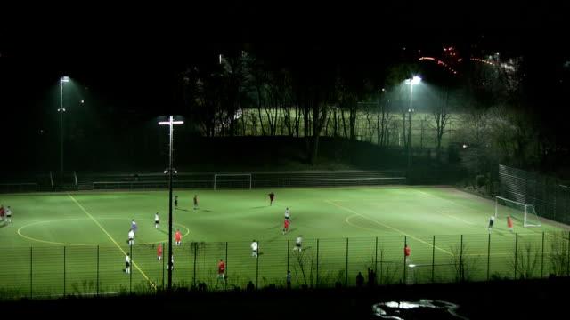 vídeos de stock e filmes b-roll de futebol à noite - iluminado por holofote