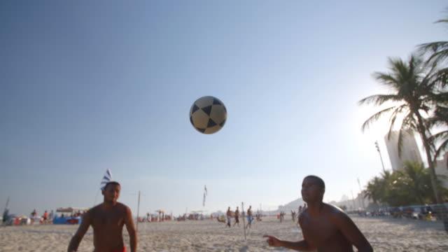 soccer ball falls through air to brazilian team in beach footvolley match - internationaler fußball stock-videos und b-roll-filmmaterial