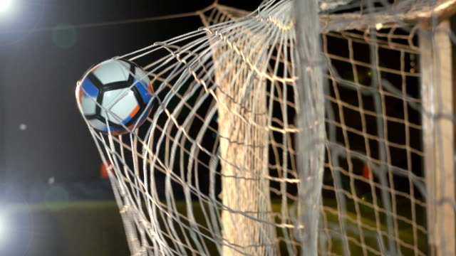 goal: soccer ball / football being scored in net - super slow motion - netting stock videos and b-roll footage
