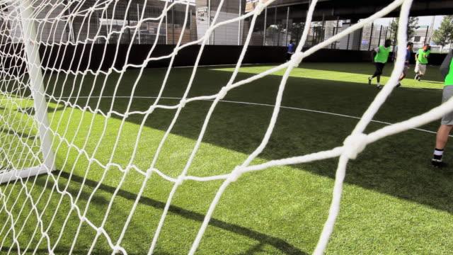 ms soccer ball hitting net, seen from behind goal post, london, uk - カーテン レース点の映像素材/bロール