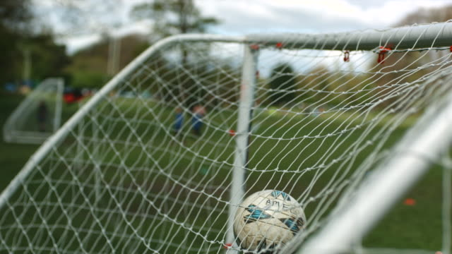 ms slo mo soccer ball hittinhg net / manchester, united kingdom   - netting stock videos & royalty-free footage