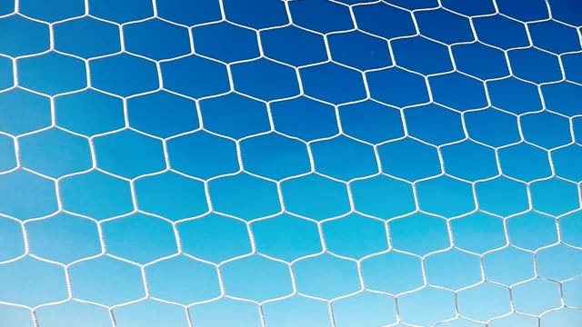 soccer ball in goal net with blue sky - netting stock videos & royalty-free footage