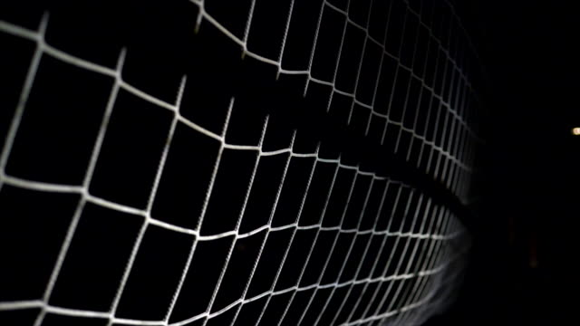 Soccer Ball Landing in Goal Net. Slow Motion Shot with Ball in the Air.