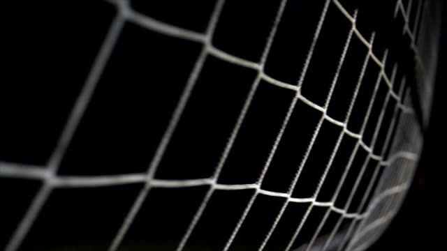 soccer ball landing in goal net. slow motion shot with ball in the air. - netting stock videos & royalty-free footage