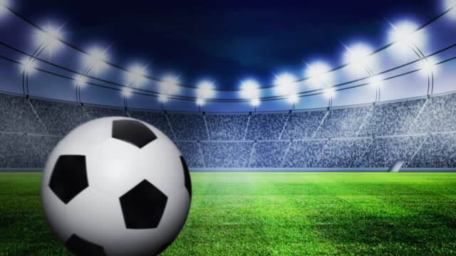 soccer ball rolling on grass in stadium at night - rotolare video stock e b–roll