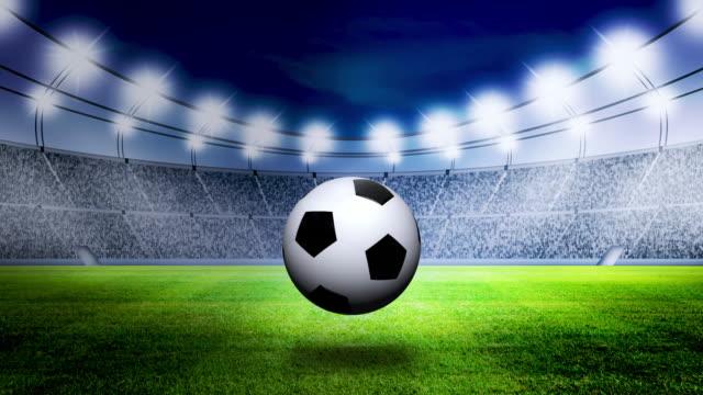vídeos de stock, filmes e b-roll de bola de futebol rolando na grama no estádio à noite - competition round