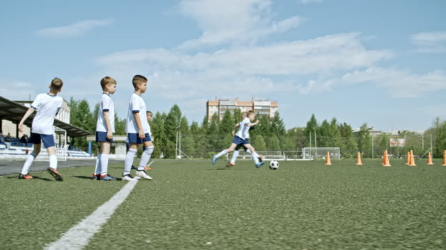 Soccer boys practicing dribbling and passing