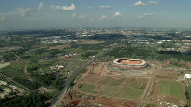 aerial soccer city, johannesburg skyline in distance / gauteng, south africa - soweto stock videos and b-roll footage