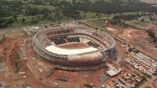 slo mo aerial soccer city stadium under construction, johannesburg, soweto, botswana - ボツワナ点の映像素材/bロール