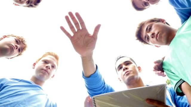 vídeos de stock e filmes b-roll de soccer coach in huddle with junior high school team on sidelines - treinador desportivo