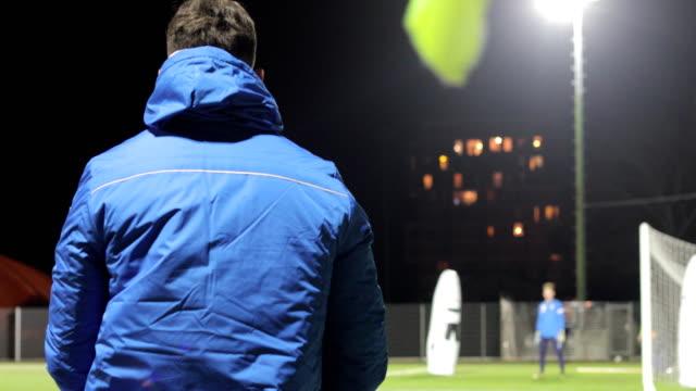 Fußball-Trainer schießen Kugeln aus Ball Canon auf Ausbildung