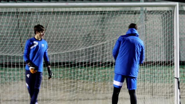 Fußball-Trainer wirft Ball zum Torwart auf Fußballtraining