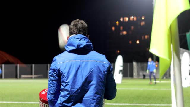 Fußball-Trainer mit Maschine, Kugeln in Richtung Torwart schießen
