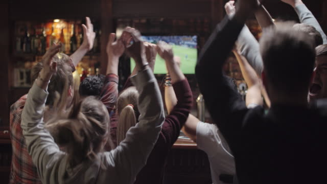 soccer fans celebrating victory of team in sports bar - bar video stock e b–roll